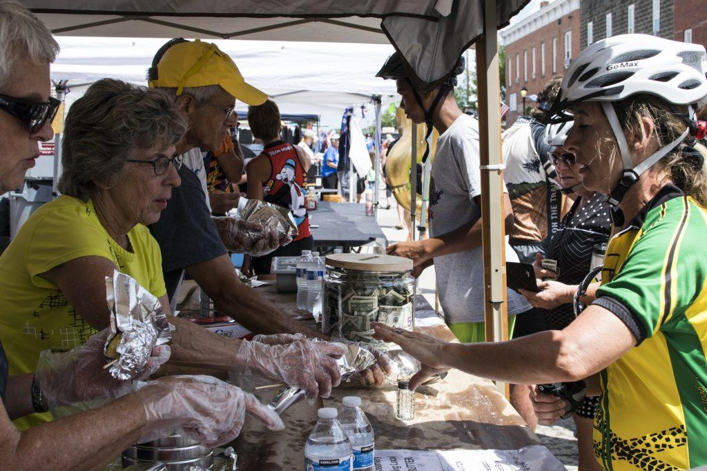 A vendor serves hunger riders on Friday, July 27, 2018. Endless foods are offered in each town along the ride. (Thomas A. Stewart/The Daily Iowan)