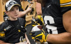 Kid Captain Garret Schuster watches his football get signed during Iowa Football Kids' Day at Kinnick Stadium on Saturday, Aug. 11, 2018.