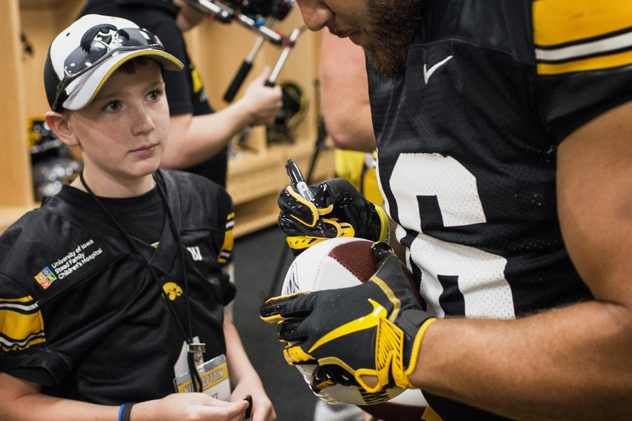 Kid+Captain+Garret+Schuster+watches+his+football+get+signed+during+Iowa+Football+Kids%27+Day+at+Kinnick+Stadium+on+Saturday%2C+Aug.+11%2C+2018.+