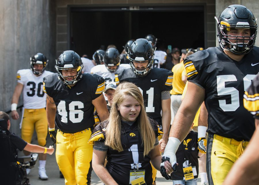 Kid Captain Livia Jackson walks with the football team during Iowa Football Kid's Day at Kinnick Stadium on Saturday, August 11, 2018. The 2018 Kid Captains met the Iowa football team and participated in a behind-the-scenes tour of Kinnick Stadium. Each child's story will be featured throughout the 2018 Iowa football season. (Katina Zentz/The Daily Iowan)