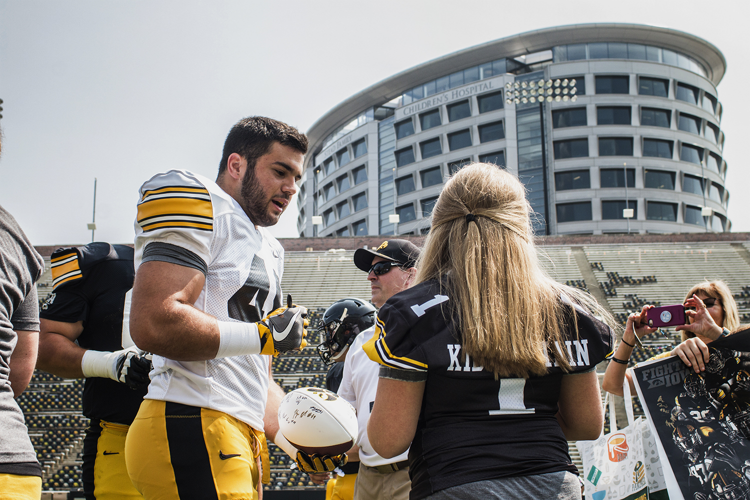 Linebacker+Jack+Hockaday+%28left%29+signs+a+football+for+Kid+Captain+Livia+Jackson+%28right%29+during+Iowa+Football+Kids%27+Day+at+Kinnick+Stadium+on+Saturday%2C+Aug.+11%2C+2018.+