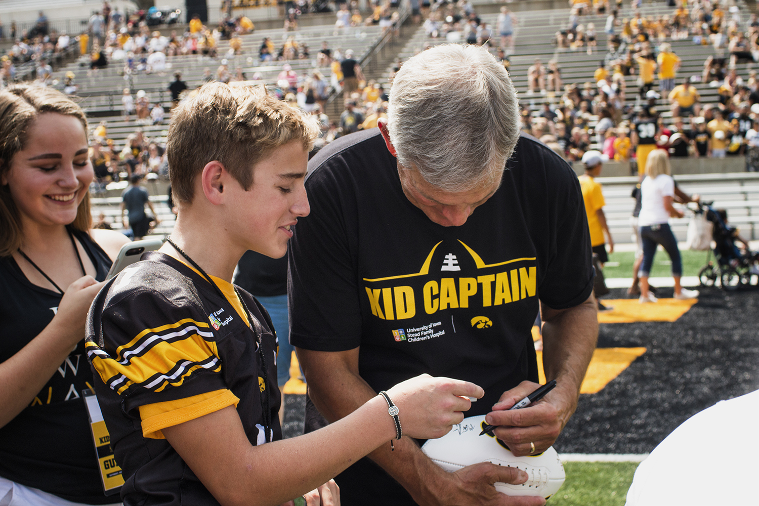 Kid+Captain+Christopher+Turnis+%28left%29+watches+Iowa+head+coach+Kirk+Ferentz+%28right%29+sign+his+football+during+Iowa+Football+Kids%27+Day+at+Kinnick+Stadium+on+Saturday%2C+Aug.+11%2C+2018.
