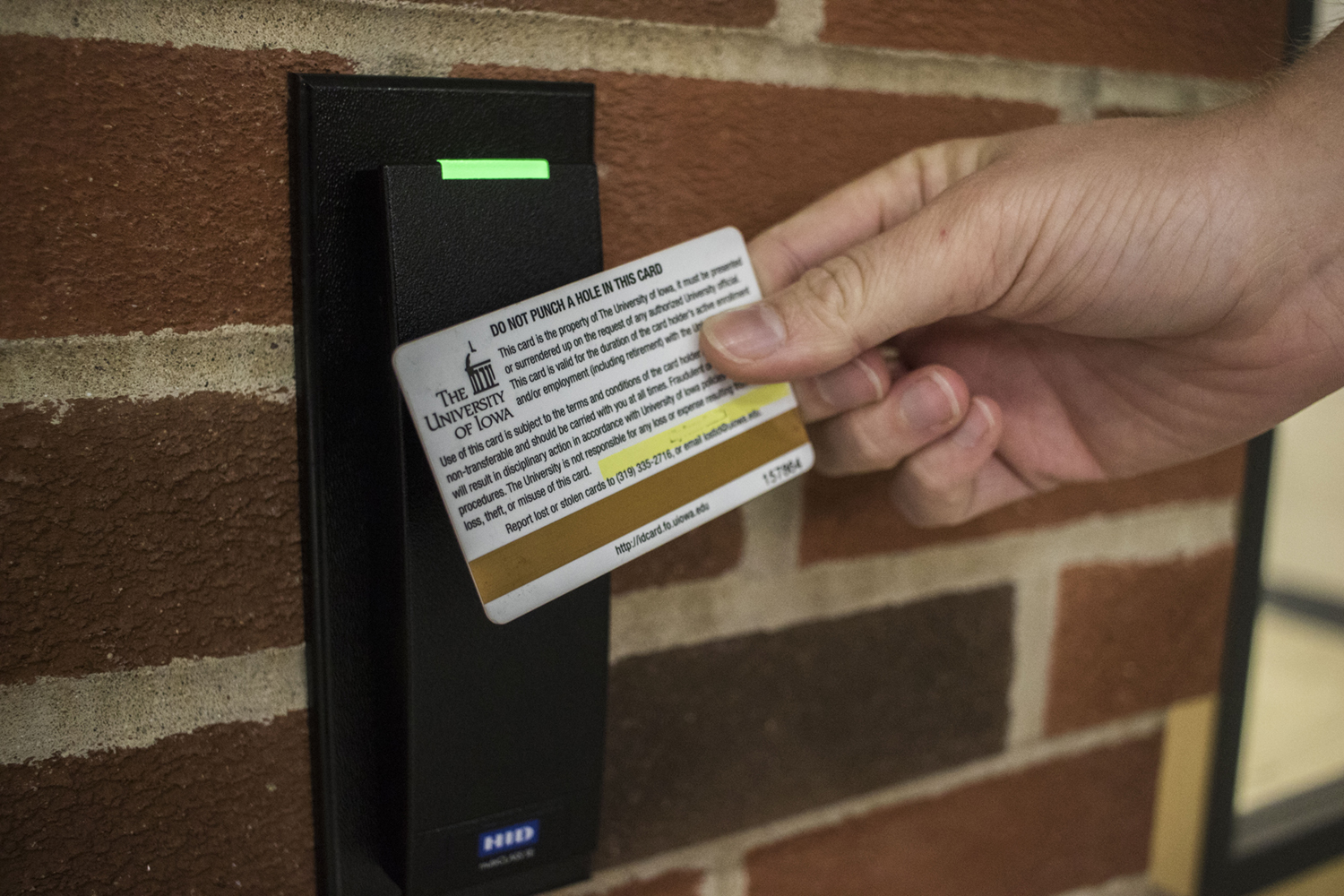 In this photo illustration, a UI ID card is seen swiping into a door.