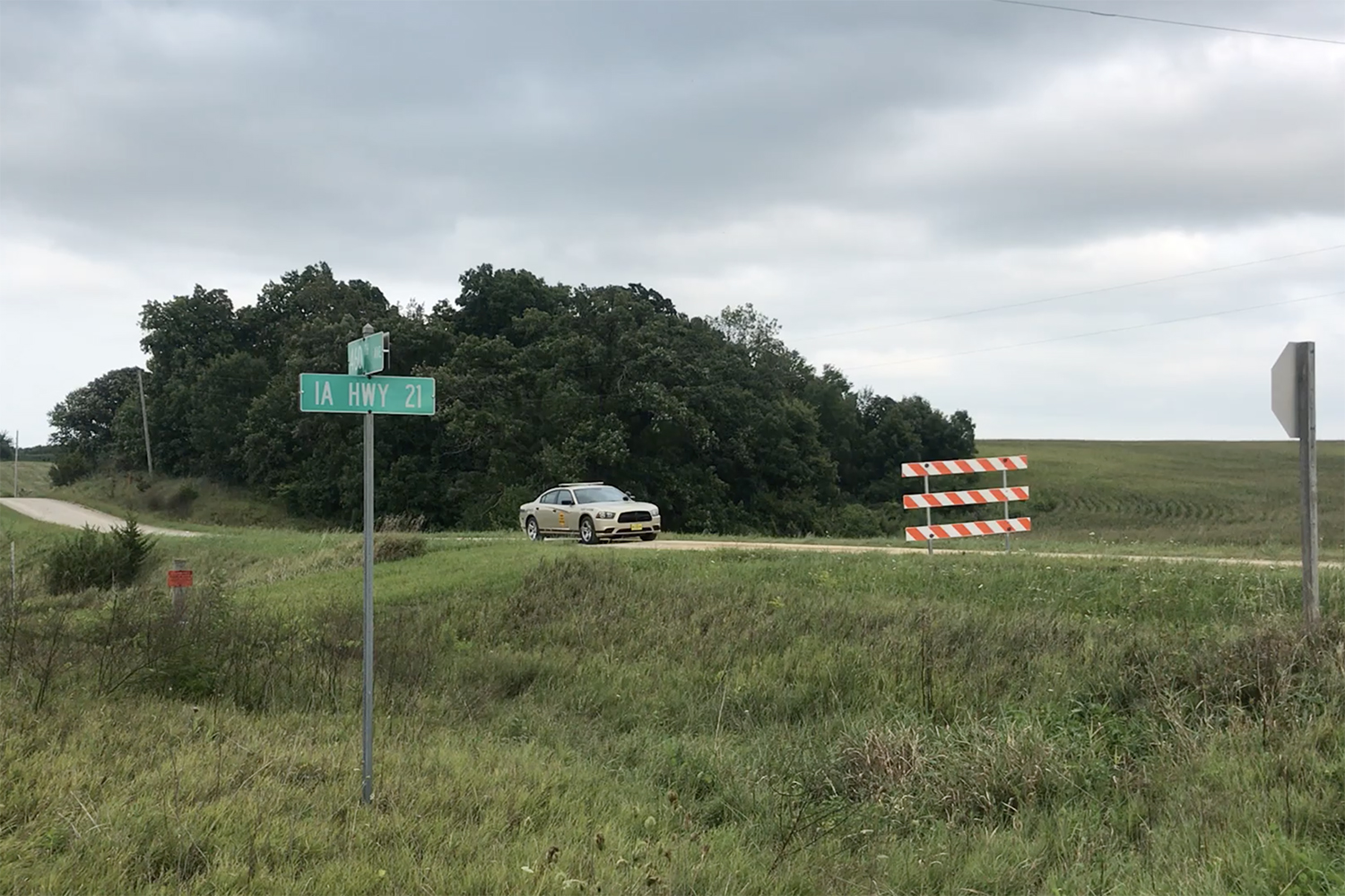 An Iowa State Patrol car sits behind a closed road sign on 385th Avenue outside of Brooklyn, Iowa near the site of where UI Mollie Tibbetts' body was found Aug. 21.