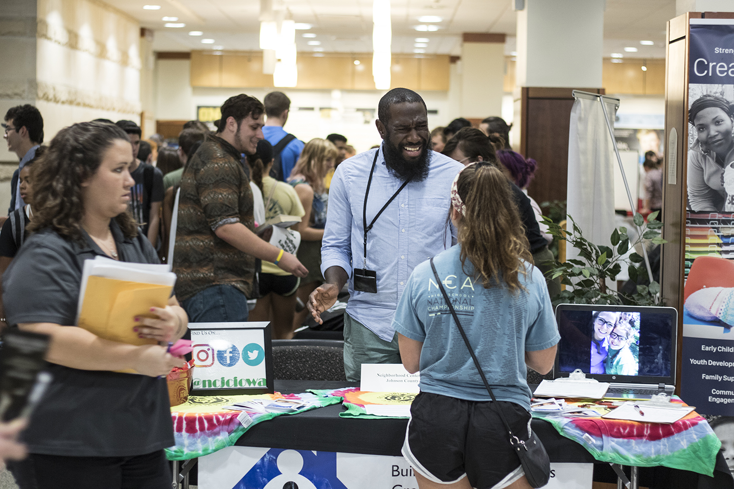 Tony Branch from the Neighborhood Centers of Johnson County speaks to an inquiring student at the student Organization Fair in the IMU on Thursday, Aug. 30, 2018.