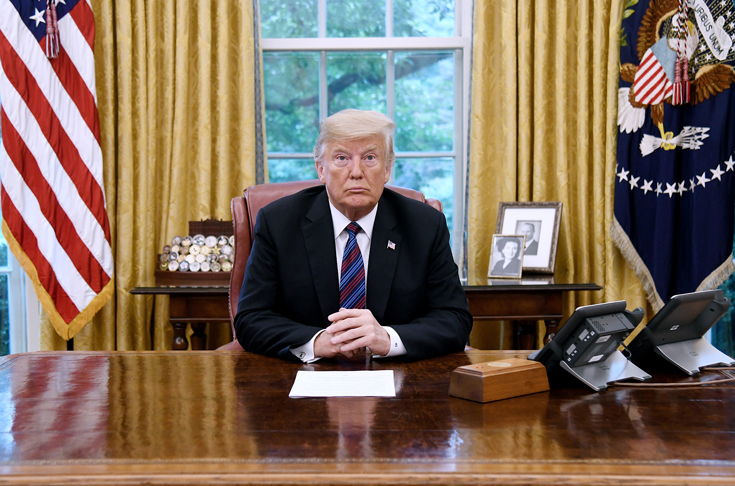 U.S. President Donald Trump listens to Mexican President Enrique Pena Nieto during a phone conversation on Monday, Aug. 27, 2018 to announce the United States-Mexico Trade Agreement in the Oval Office of the White House in Washington, D.C.