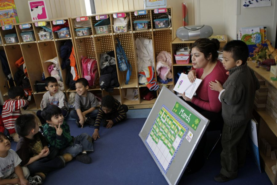 Gustavo Guzman, 4, right, leans on his teacher, Janeth Medellin as she tests her students on the months of the year in English and Spanish, in her pre-K class at Casa Infantil in the Logan Square neighborhood, March 25, 2009, in Chicago, Illinois.  (José M. Osorio/Chicago Tribune/MCT)