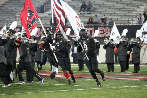 Northern Illinois football players run out on to the field before a game.