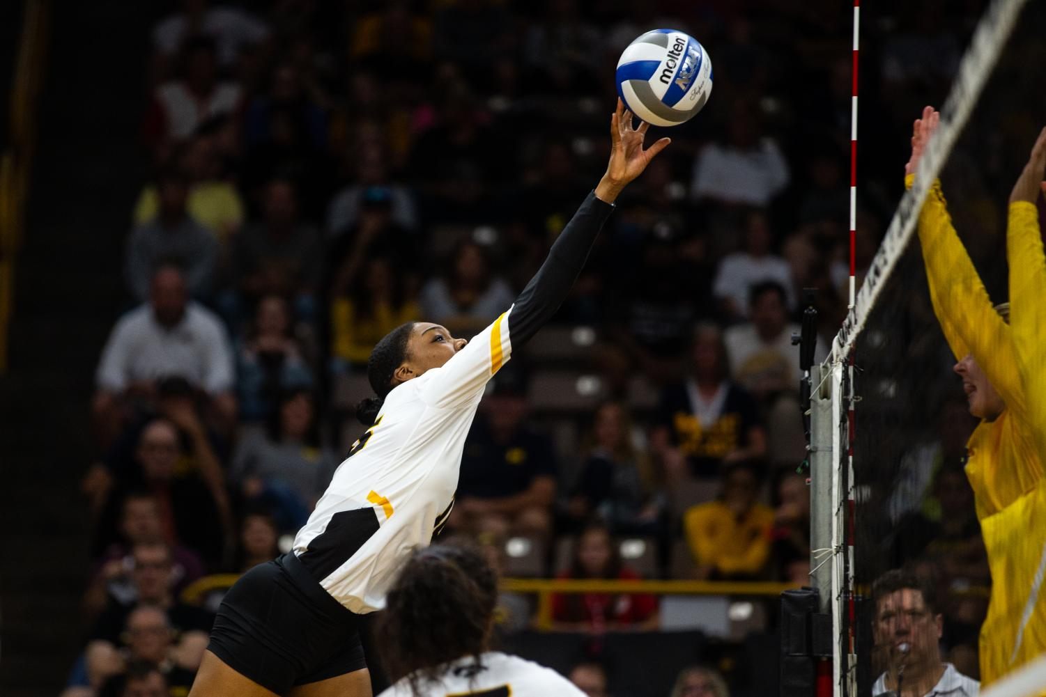Taylor Louis tips the ball over the net during Iowa's match against Michigan at Carver-Hawkeye Arena on September 23, 2018. The Hawkeyes were defeated 3-1. (Megan Nagorzanski/The Daily Iowan)