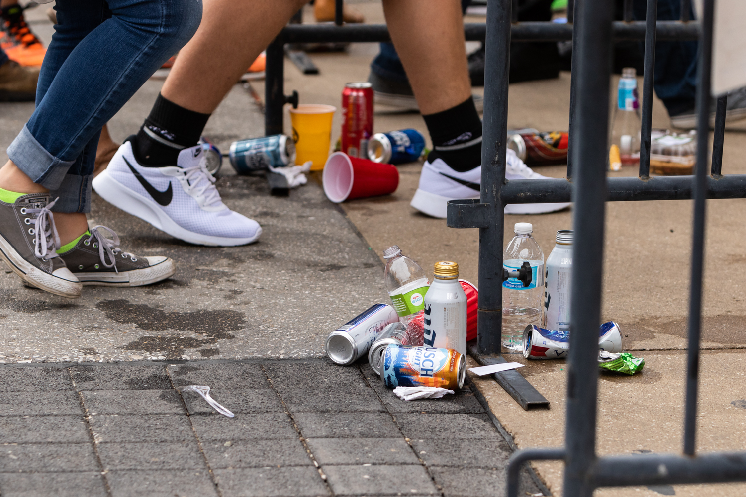 Fans walk past empty beer cans and cups as they enter Kinnick Stadium before a football game against Iowa State University on Saturday, Sept. 8, 2018.