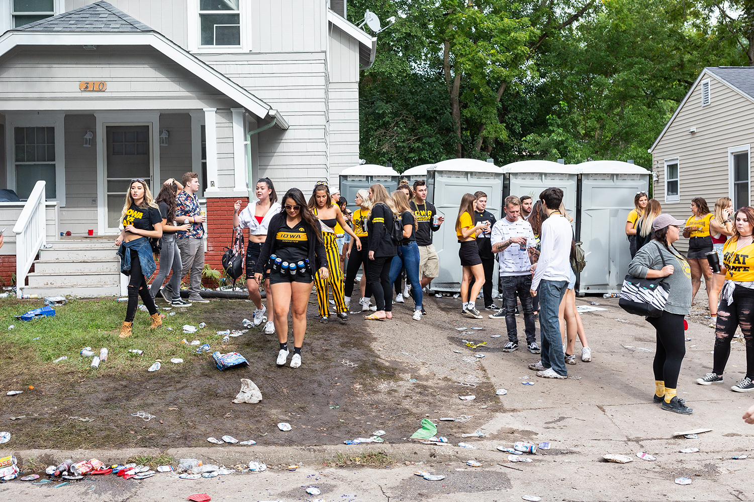 Tailgaters walk out of a party before a football game against Iowa State University on Saturday, Sept. 8, 2018.