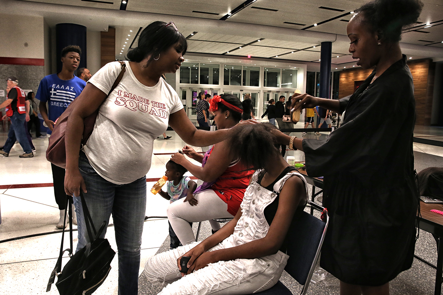 Yvonne Ferguson-Smith helps with her daughter Yasmin's haircut inside the George R. Brown Convention Center on Aug. 31, 2017. Meka Fisher, of Laced Up By Meka hair salon, volunteered with nearly a dozen other barbers and hairdressers to at the main Hurricane Harvey evacuation center. (Robert Gauthier/Los Angeles Times/TNS)