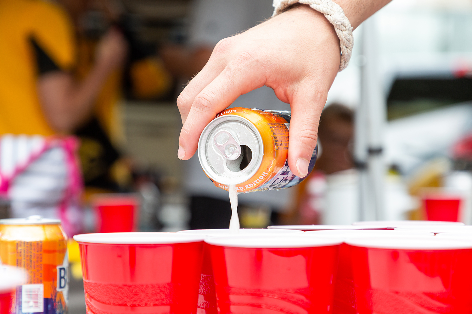 A tailgater pours out a beer for beer pong in Iowa City on Saturday, Sept. 1, 2018.