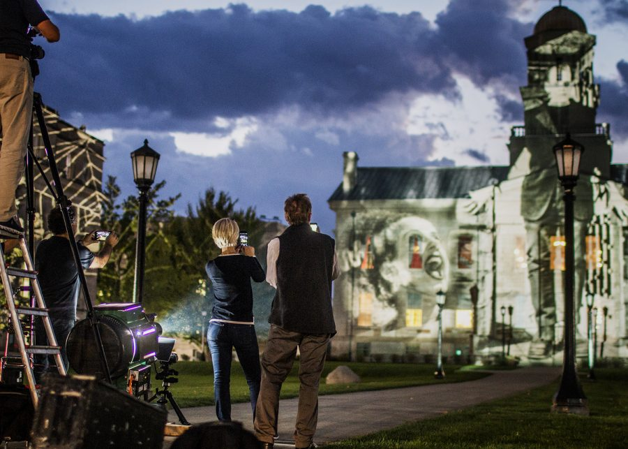 "Crew members take photos of the art projected onto the Old Capitol on Wednesday, October 3, 2018. International light artist Gerry Hofstetter chose the building as a backdrop to feature artwork included in his ""Light Art Grand Tour USA."""