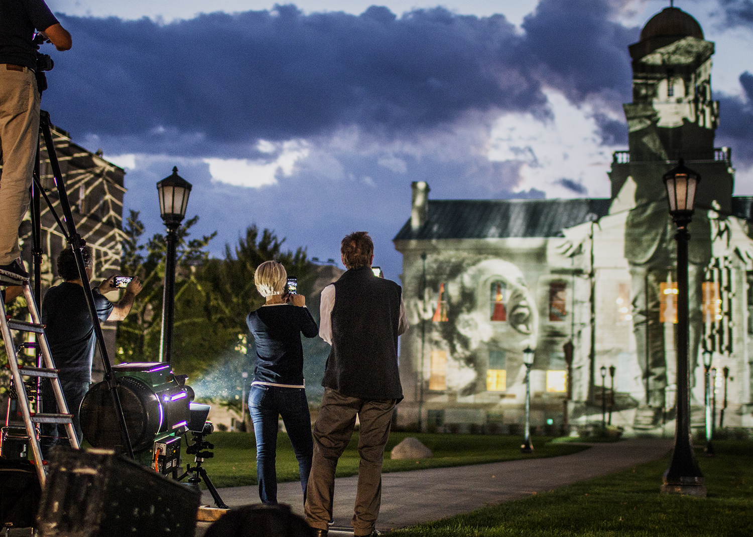 """Crew members take photos of the art projected onto the Old Capitol on Wednesday, October 3, 2018. International light artist Gerry Hofstetter chose the building as a backdrop to feature artwork included in his """"Light Art Grand Tour USA."""""""