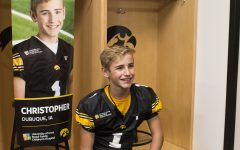 Kid Captain Christopher Turns smiles front of his banner during Iowa Football Kid's Day at Kinnick Stadium on Saturday, August 11, 2018. The 2018 Kid Captains met the Iowa football team and participated in a behind-the-scenes tour of Kinnick Stadium. Each child's story will be featured throughout the 2018 Iowa football season.