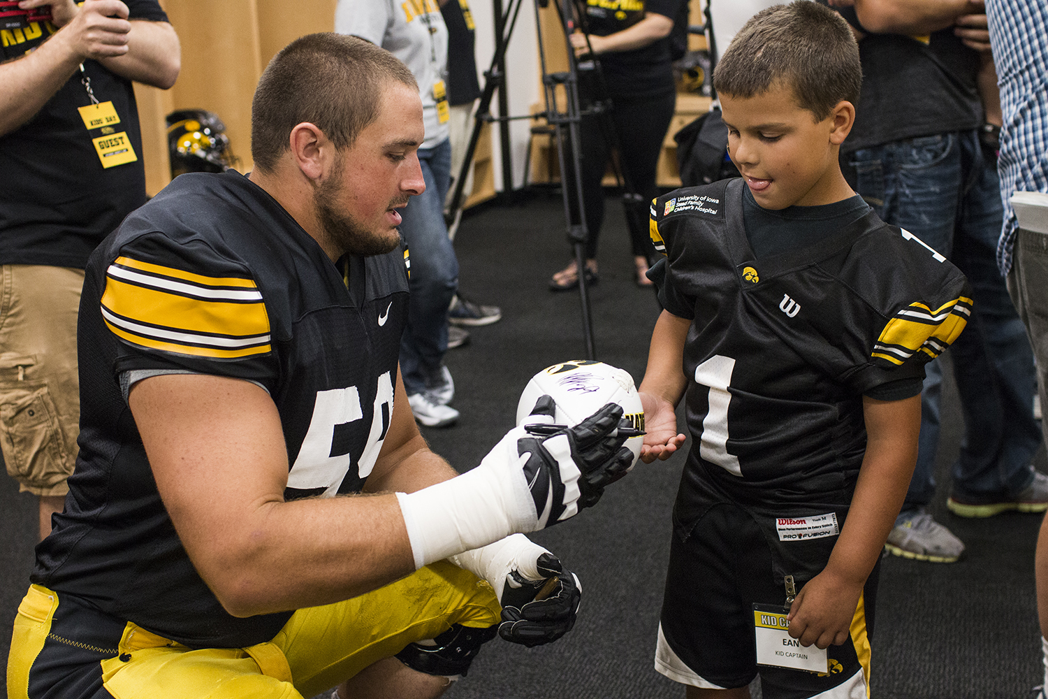 Offensive lineman Ross Reynolds (left) signs a football for Kid Captain Ean Gorsh (right) during Iowa Football Kid's Day at Kinnick Stadium on Saturday, August 11, 2018. The 2018 Kid Captains met the Iowa football team and participated in a behind-the-scenes tour of Kinnick Stadium. Each child's story will be featured throughout the 2018 Iowa football season.