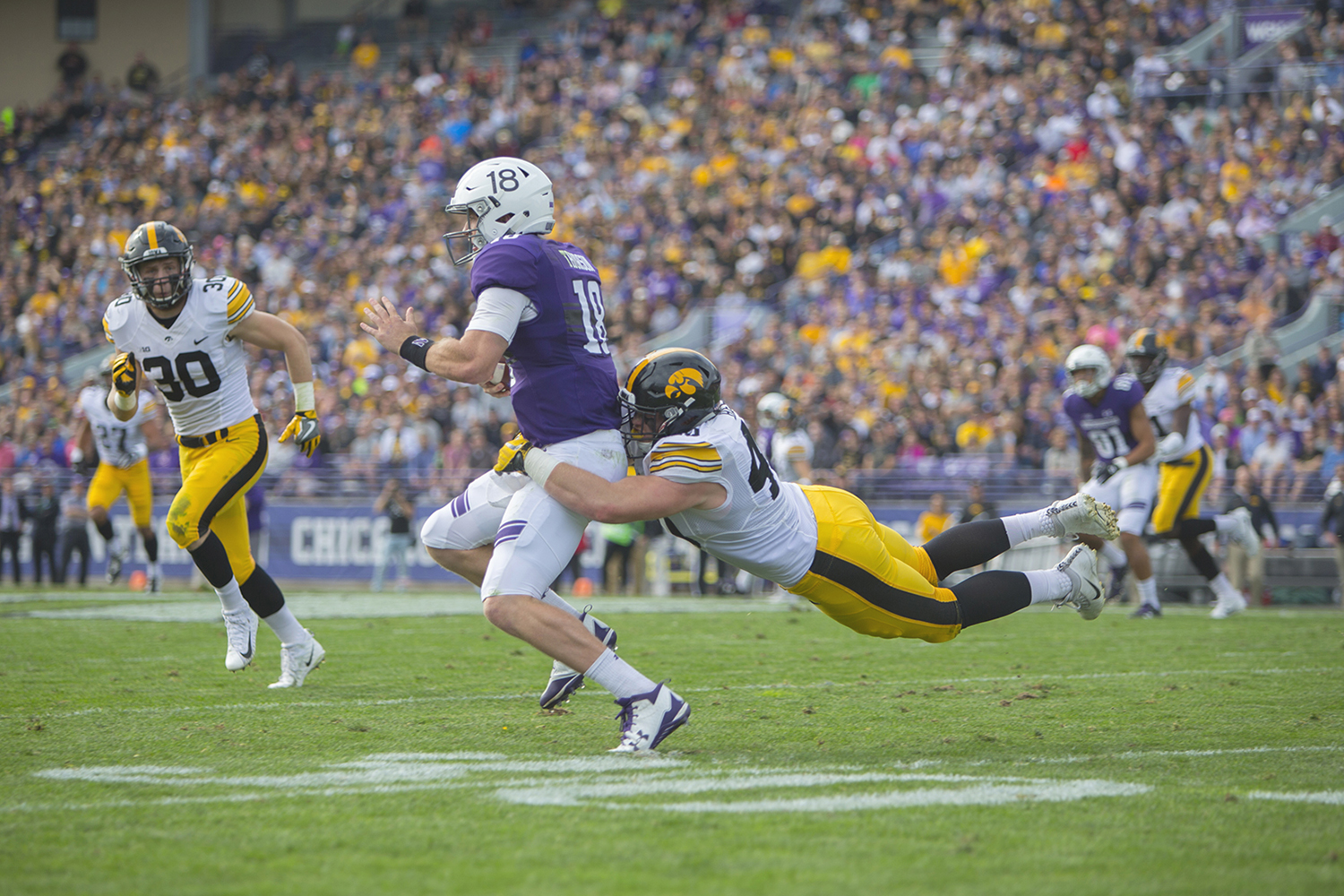 Iowa defensive end Parker Hesse tackles Northwestern quarterback Clayton Thorson during the game between Iowa and Northwestern at Ryan Field in Evanston on Saturday, Oct. 21, 2017.