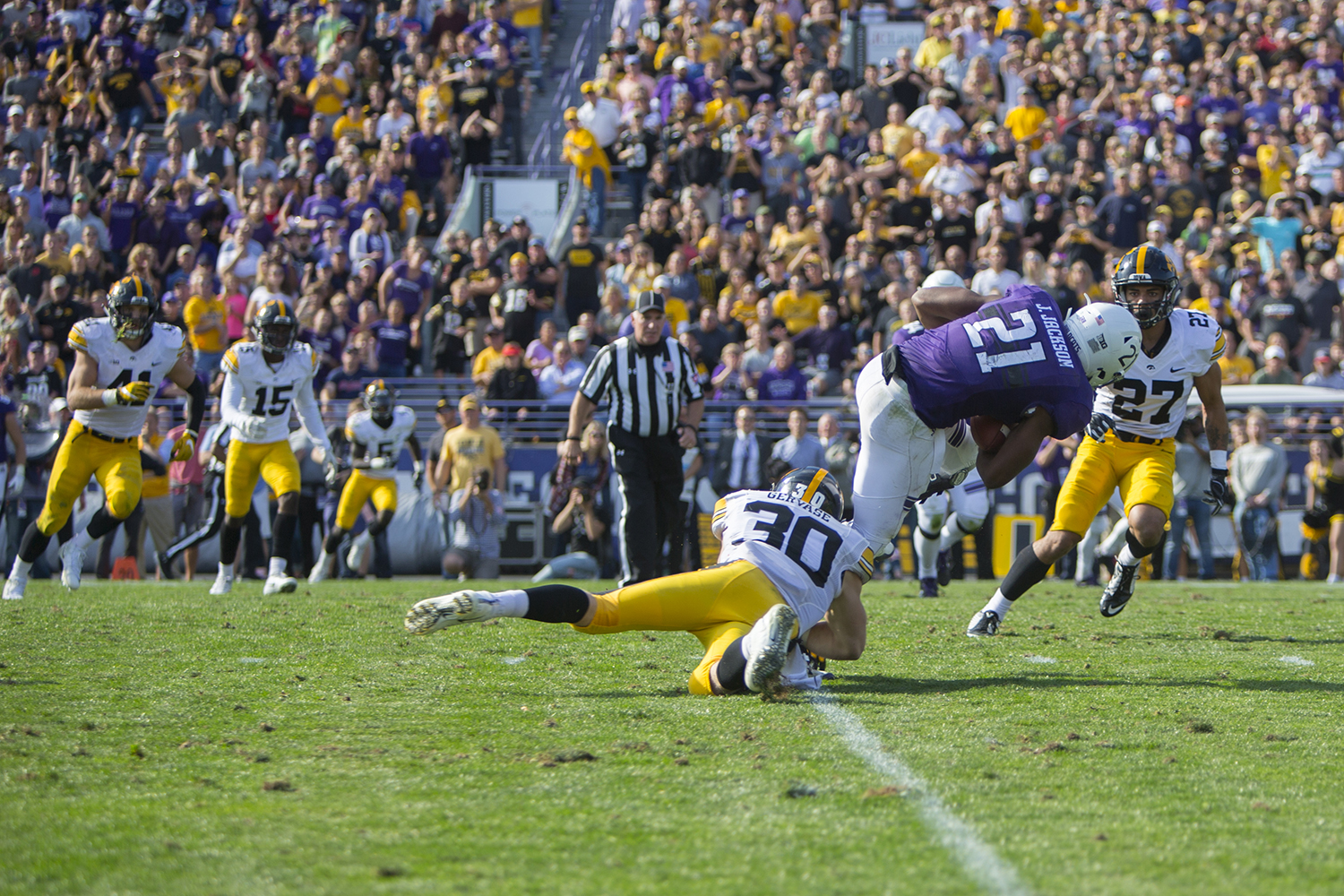 Iowa defensive back Jake Gervase tackles Northwestern running back Justin Jackson during the game between Iowa and Northwestern at Ryan Field in Evanston on Saturday, Oct. 21, 2017. The Wildcats defeated the Hawkeyes, 17-10, in overtime.