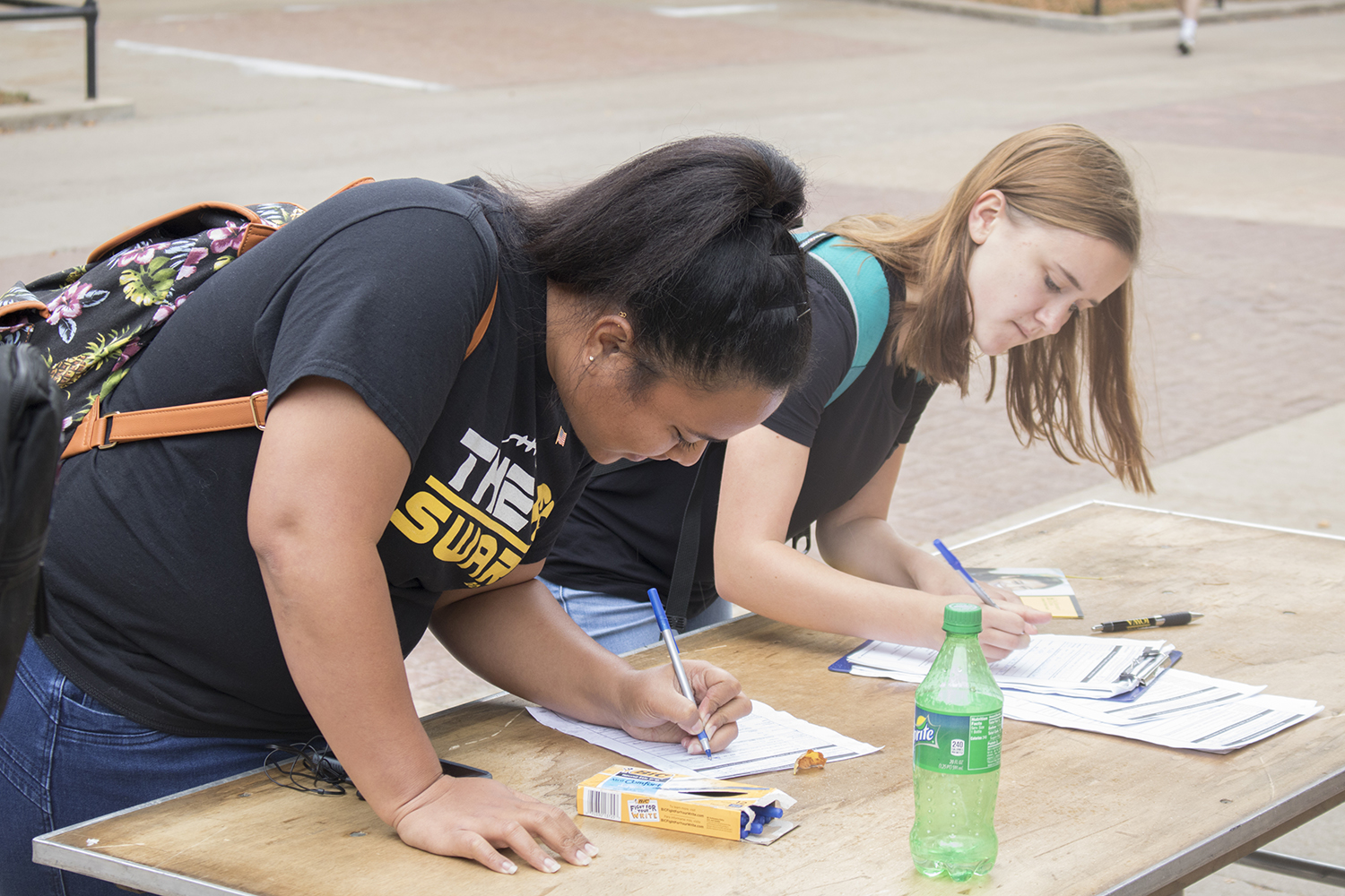Students fill paperwork on the T. Anne Cleary Walkway on Tuesday, September 26, 2017. UISG hosted tables where students could register to vote.