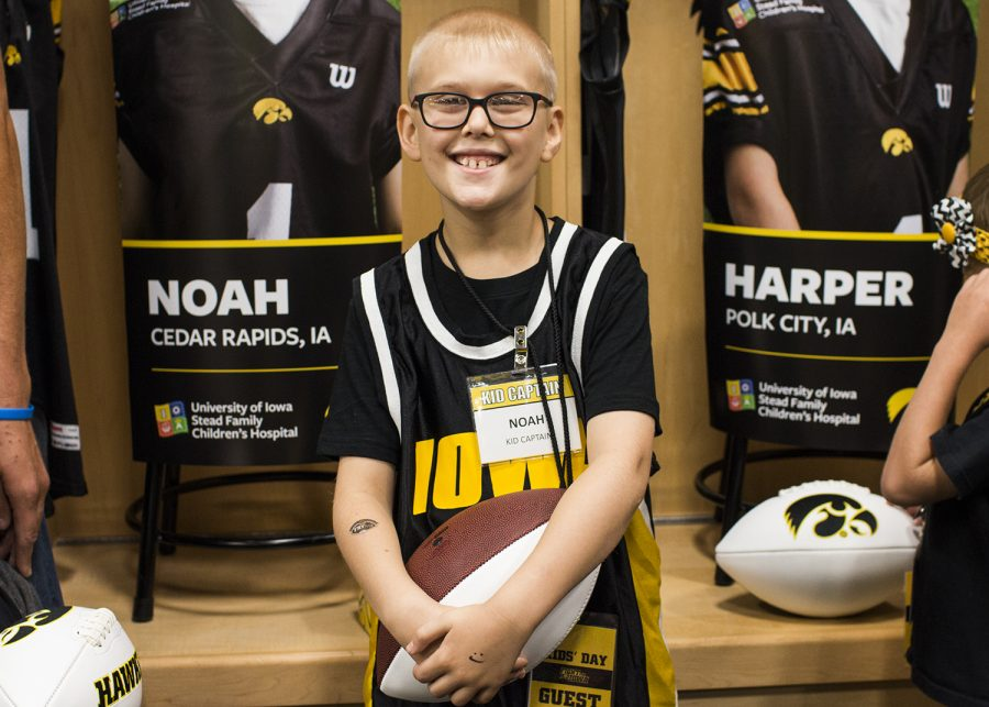 Kid+Captain+Noah+Hodgins+stands+in+front+of+his+banner+during+Iowa+Football+Kids+Day+at+Kinnick+on+Aug.+11.