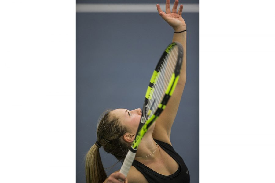 Iowa freshman Danielle Burich tosses up a serve during the NCAA women's tennis match between Iowa and Creighton at the Hawkeye Tennis and Recreation Complex on Saturday, Jan. 20, 2018. The season opener for Iowa ended with a victory against the Bulldogs 6-1.