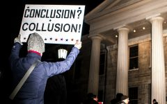 An attendee holds up a sign referencing possible Russian collusion in the 2016 Presidential election during the