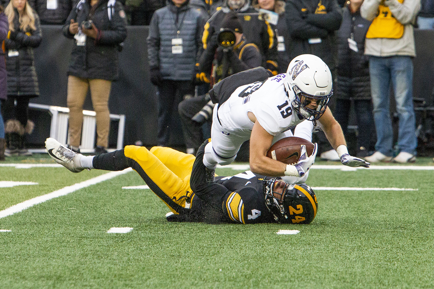 Northwestern wide receiver Riley Lees jumps over Iowa defensive back Josh Turner during the Iowa/Northwestern game at Kinnick Stadium on Saturday, November 10, 2018. The Wildcats defeated the Hawkeyes 14-10. (Katina Zentz/The Daily Iowan)