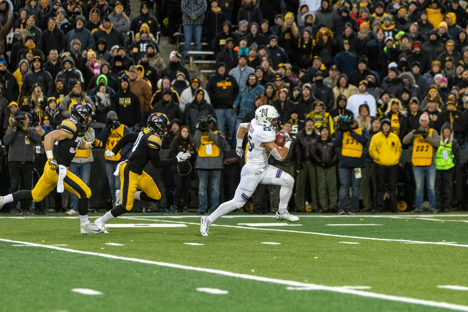 Northwestern+running+back+Isaiah+Bowser+%2325+runs+away+from+the+Iowa+defense+during+a+game+against+Iowa+on+Saturday%2C+Nov.+10%2C+2018+at+Kinnick+Stadium+in+Iowa+City.+Bowser+would+score+on+this+play+and+the+Wildcats+defeated+the+Hawkeyes+14-10.+%28David+Harmantas%2FThe+Daily+Iowan%29