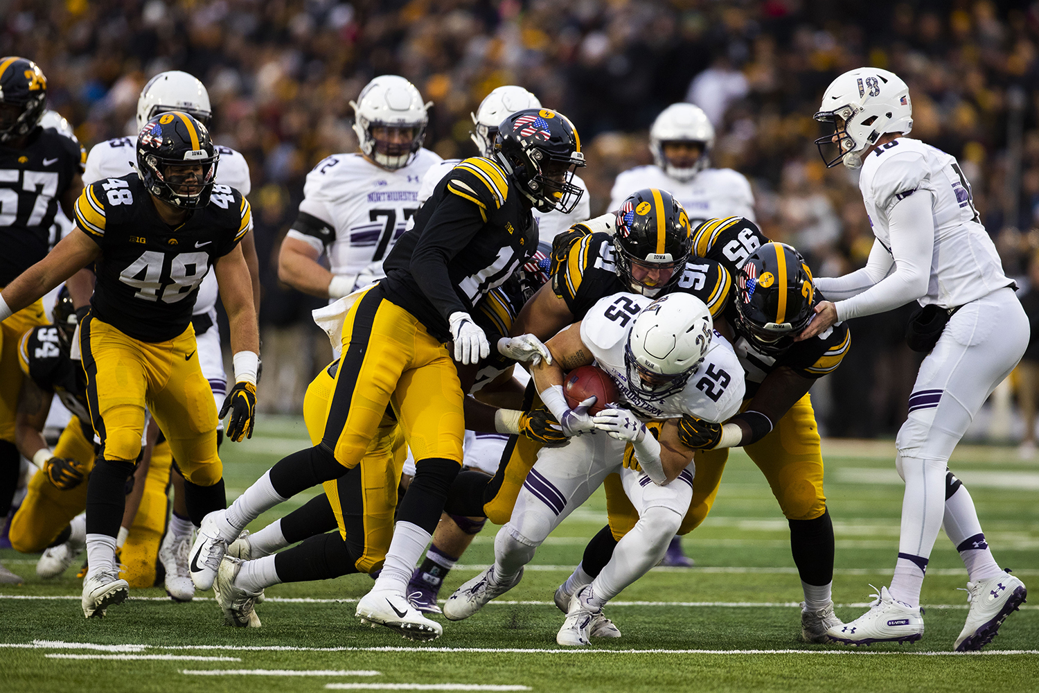 Northwestern's Isaiah Bowser is tackled by Iowa defense during the Iowa/Northwestern football game at Kinnick Stadium on Saturday, November 10, 2018. The Wildcats defeated the Hawkeyes, 14-10. (Lily Smith/The Daily Iowan)