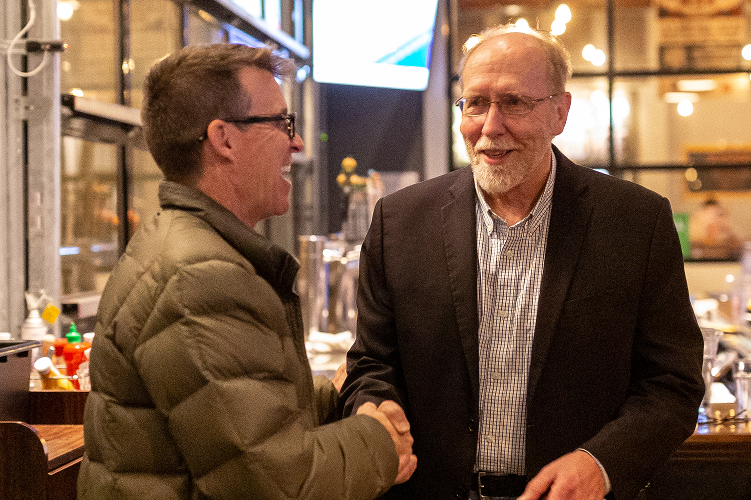 Congressman Dave Loebsack (D-IA) (center) shakes hands with Iowa State Senator Joe Bolkcom at an election night watch party at Big Grove Brewery in Iowa City on Tuesday, Nov. 6, 2018. (David Harmantas/The Daily Iowan)