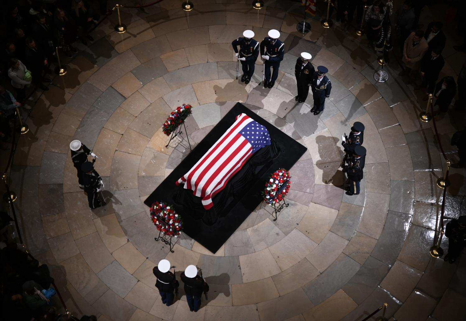 Joint services military honor guards stand next to the flag-draped casket of former U.S. President George H.W. Bush on the Lincoln catafalque during a memorial service at the Capitol Rotunda on Dec. 3, 2018 in Washington, D.C. (Olivier Douliery/Abaca Press/TNS)