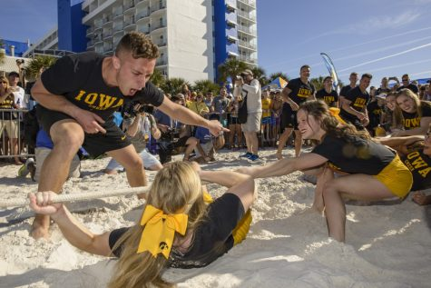 An Iowa spirit squad member encourages a teammate during a tug of war against Mississippi State's cheerleaders at Outback Bowl Beach Day at the Hilton Clearwater Beach Resort in Clearwater, Florida on Sunday December 30, 2018. The day's festivities included a variety of events for fans and general merrymaking