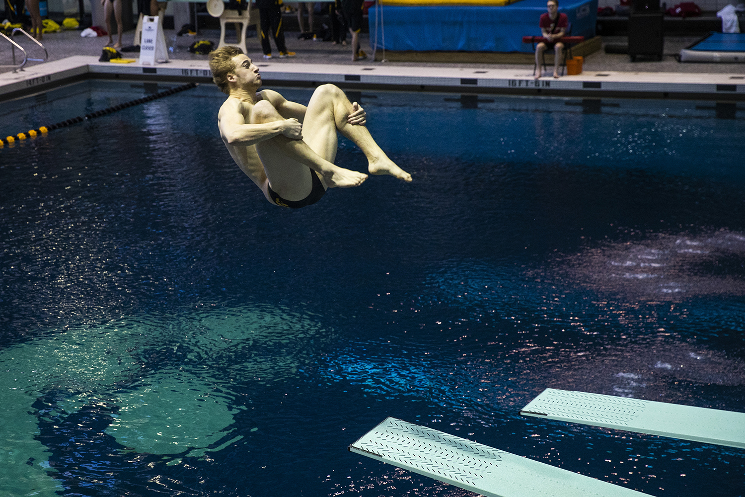 Iowa diver Will Brenner flips in the air during the Northwestern/Wisconsin swim meet at the Campus Recreation and Wellness Center on Saturday, January 19, 2019. The men's swimming and diving team defeated the Badgers, 164-136, and the Wildcats, 194-106. The women's swimming and diving team fell to the Badgers, 191-109, and the Wildcats, 178-122.