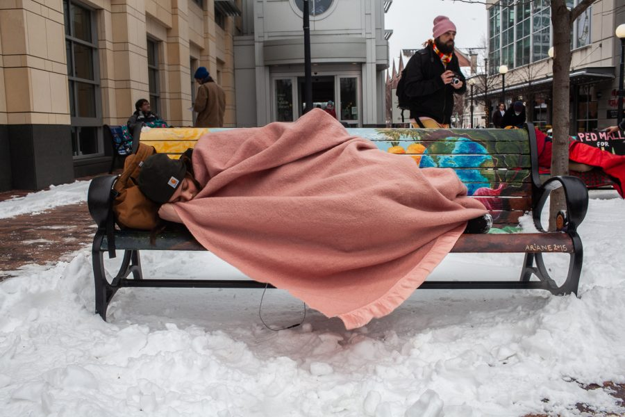 Demonstrators+lay+on+benches+during+a+%22Sleep+In%22+demonstration+in+the+Pedestrian+Mall+in+Iowa+City+on+Monday%2C+January+14%2C+2019.+The+benches+have+been+in+the+works+since+2014%2C+but+were+installed+in+November+of+2018.+%28Wyatt+Dlouhy%2FThe+Daily+Iowan%29