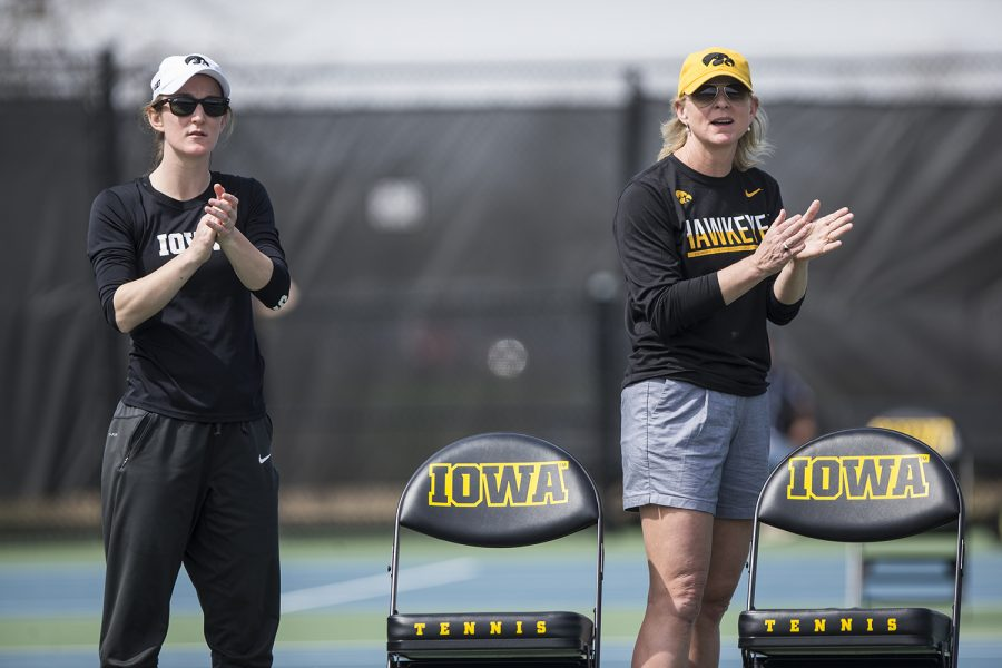 Iowa head coach Sasha Schmid and strength coach Lindsay Winkelman cheer on the Hawks during the match against Penn State at Hawkeye Tennis and Recreation Complex on Sunday, April 9.