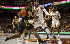 Iowa center Tyler Cook (25) dribbles past Minnesota forward Eric Curry (24) during the men's basketball game vs. Minnesota at Williams Arena on Sunday, January 27, 2019.