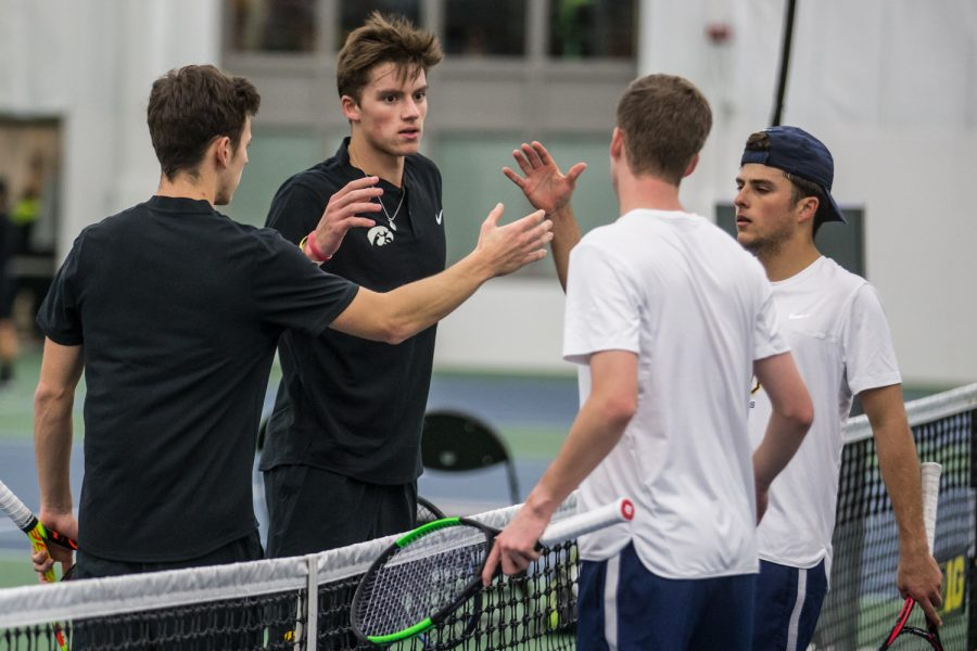 Players+shake+hands+following+a+doubles+set+during+a+men%27s+tennis+match+between+Iowa+and+Marquette+on+Saturday%2C+January+19%2C+2019.+The+Hawkeyes+swept+the+Golden+Eagles%2C+7-0.