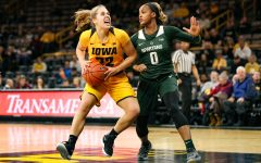 Iowa guard Kathleen Doyle (22) fights through a defender during a basketball game against Michigan State on Thursday, Feb. 7, 2019. The Hawkeyes defeated the Spartans 86-71.