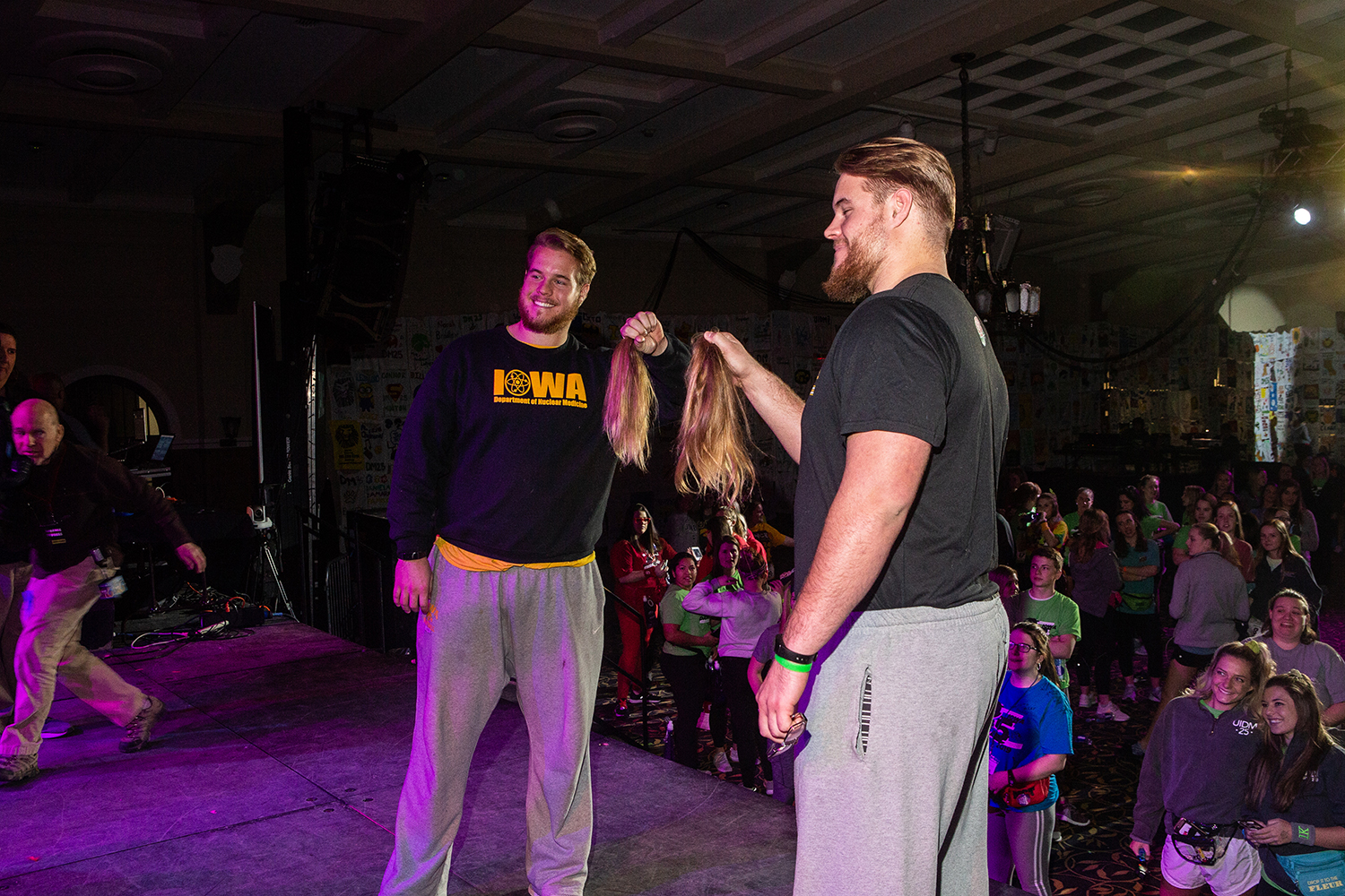 Landon (left) and Levi Paulson (right) hold up their hair during Dance Marathon 25 at the Iowa Memorial Union on Saturday, Feb. 2, 2019. After Landon's girlfriend Alexis Henry raised over $10,000 for the Big Event, the twins committed to losing their locks.
