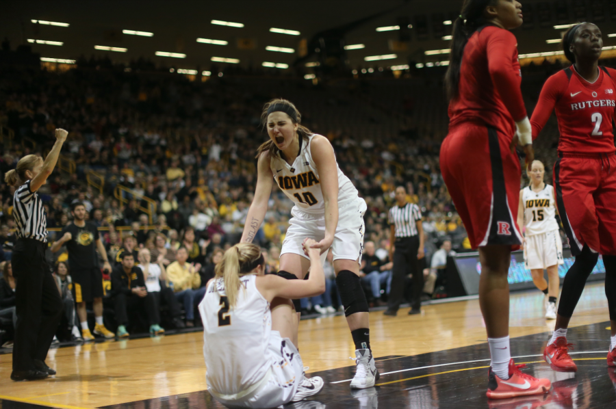 Iowa center Megan Gustafson helps teammate Ally Disterhoft up after getting fouled against Rutgers during the Iowa-Rutgers game in Carver-Hawkeye Arena on Monday, Jan. 4, 2016. The Hawkeyes defeated the Scarlet Knights, 69-65.