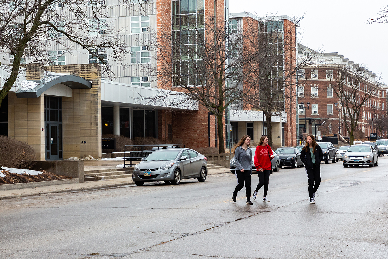 Pedestrians jaywalk across Clinton St. in front of Burge residence hall on Sunday, Feb. 3, 2019. The lack of marked crosswalks on this street prevents pedestrians from crossing in an orderly manner.