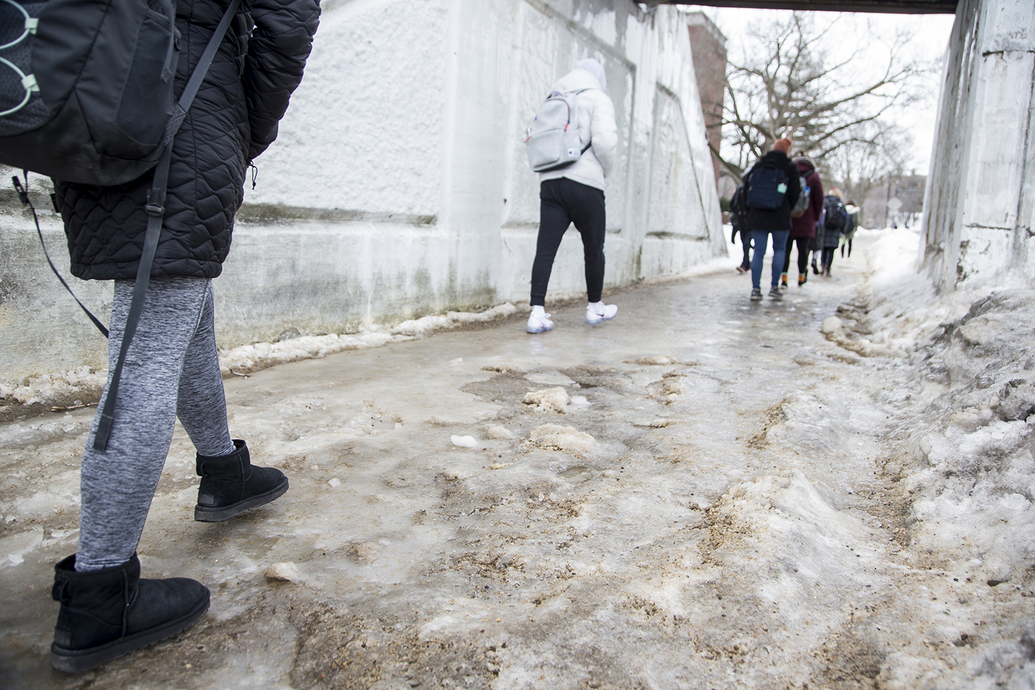 Students walk across a sheet of ice in Iowa City on Monday, February 25, 2019. Ice froze over pavements after the rainy weekend, but Iowa City is running out of salt to clear sidewalks.