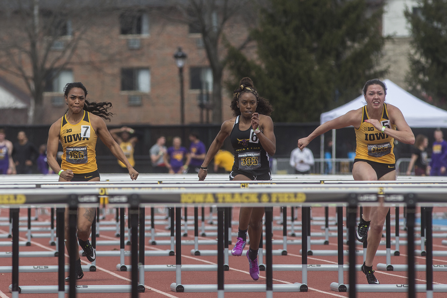 From left: Iowa's Tria Seawater-Simmons, Minnesota State's Alexis Smith, and Iowa's Jenny Kimbro compete in the women's 100 meter hurdles during the 19th annual Musco Twilight meet at the Francis X. Cretzmeyer Track in Iowa City on Thursday, April 12. Kimbro finished first with the time of 13.77.