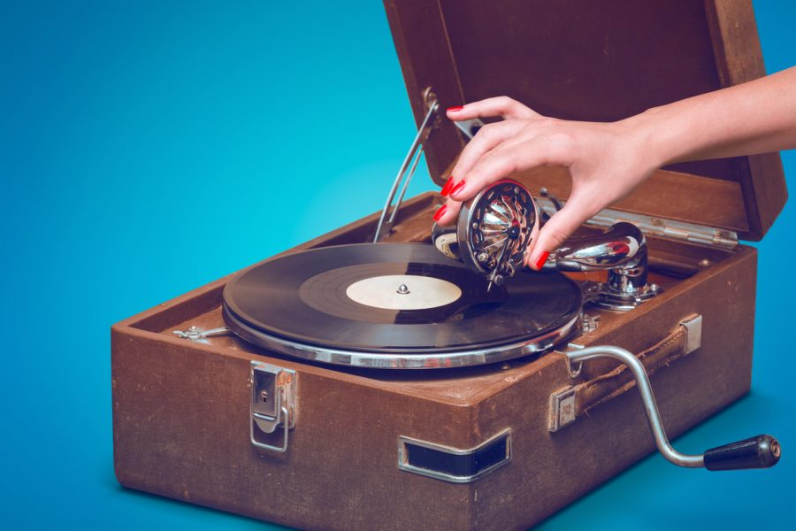 Old+portable+gramophone+with+female+hand+pin-up+styled+isolated%2C+on+blue+background+with+empty+space