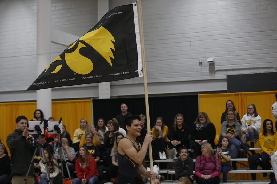 Evan Davis parades the flag around the parallel bars as a teammate sticks a perfect landing and gets to ring the bell during the meet against Nebraska at the UI Field House on Saturday, March 2, 2019. Iowa took the victory with a score of 406.500 over Nebraska with a score of 403.550.