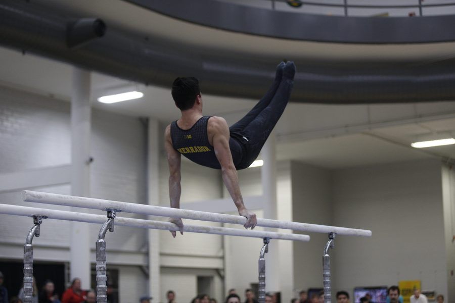 Andrew Herrador competes on the parallel bars during the meet against Nebraska at the UI Field House on Saturday, March 2, 2019. Iowa took the victory with a score of 406.500 over Nebraska with a score of 403.550.