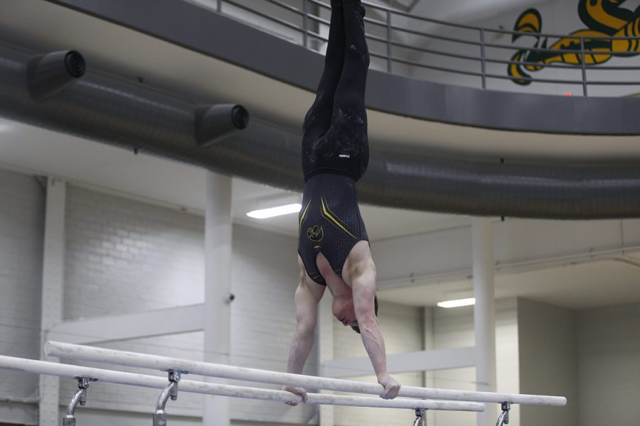 Stewart Brown performs on the parallel bars during the meet against Nebraska at the UI Field House on Saturday, March 2, 2019. Iowa took the victory with a score of 406.500 over Nebraska with a score of 403.550.