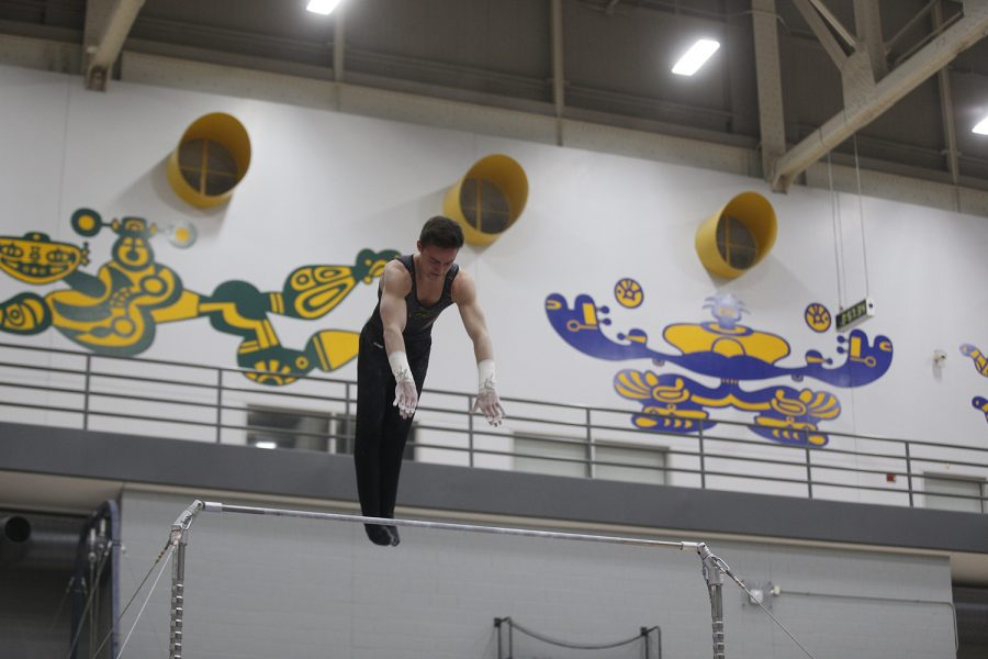 Mitch Mandozzi competes on the high bar during the meet against Nebraska at the UI Field House on Saturday, March 2, 2019. Iowa took the victory over Nebraska 406.700 to 403.550.