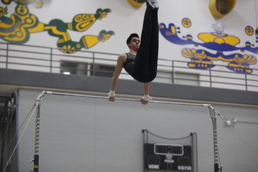 Andrew Herrador competes on the high bar during the meet against Nebraska at the UI Field House on Saturday, March 2, 2019. Herrador got a score of 13.100 on high bar, and placed first in the all around competition with a 79.850, a career best. Iowa took the victory over Nebraska 406.700 to 403.550.
